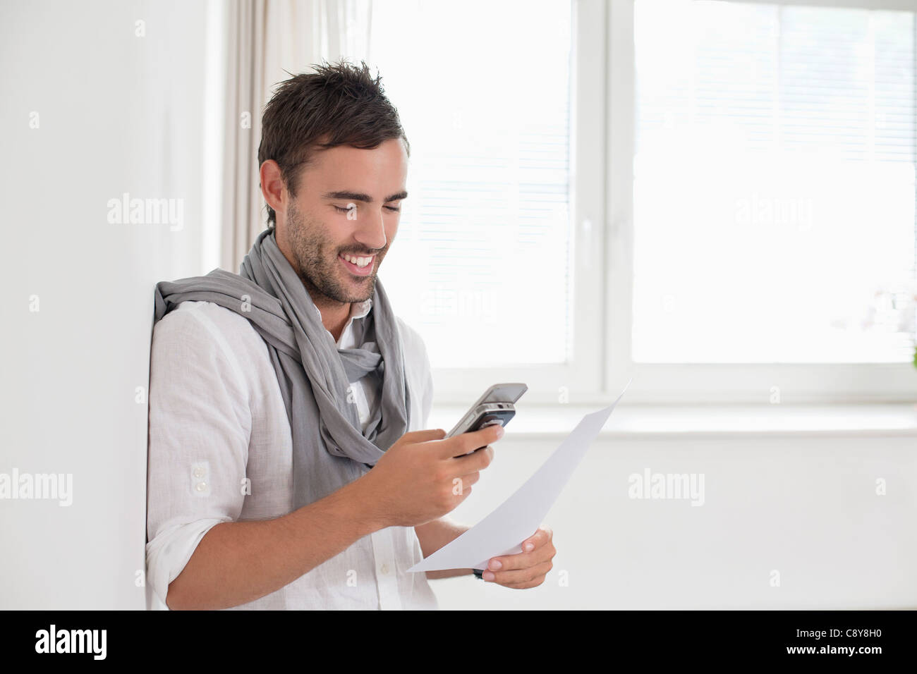 portrait of young man in empty room with mobile phone - Stock Image
