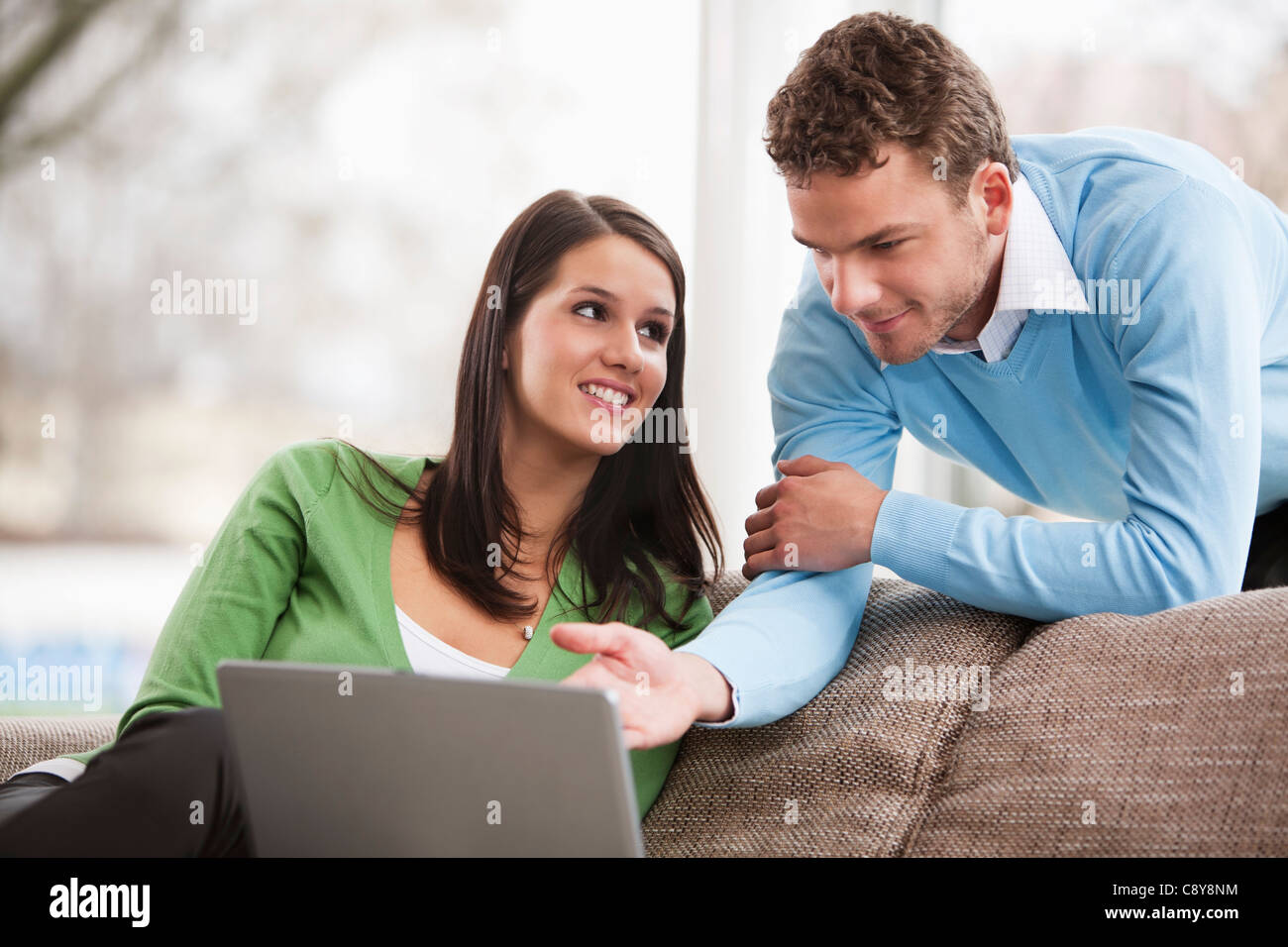 portrait of young couple with laptop computer at home - Stock Image