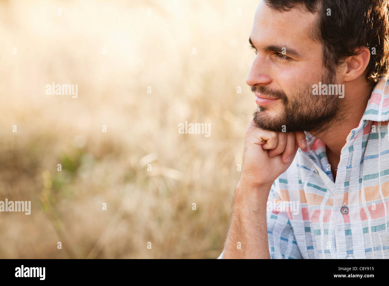 portrait of young man in front of field - Stock Image