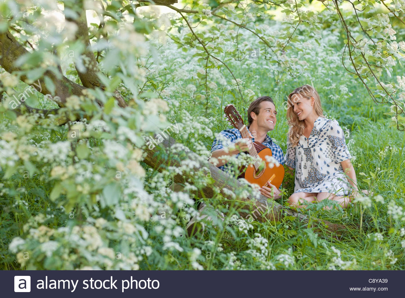 Man playing guitar for girlfriend in forest - Stock Image