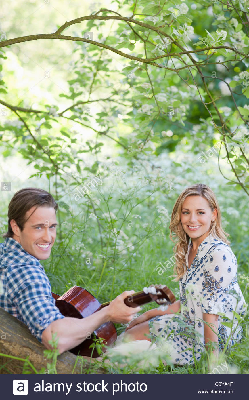 Man playing guitar for girlfriend in park - Stock Image