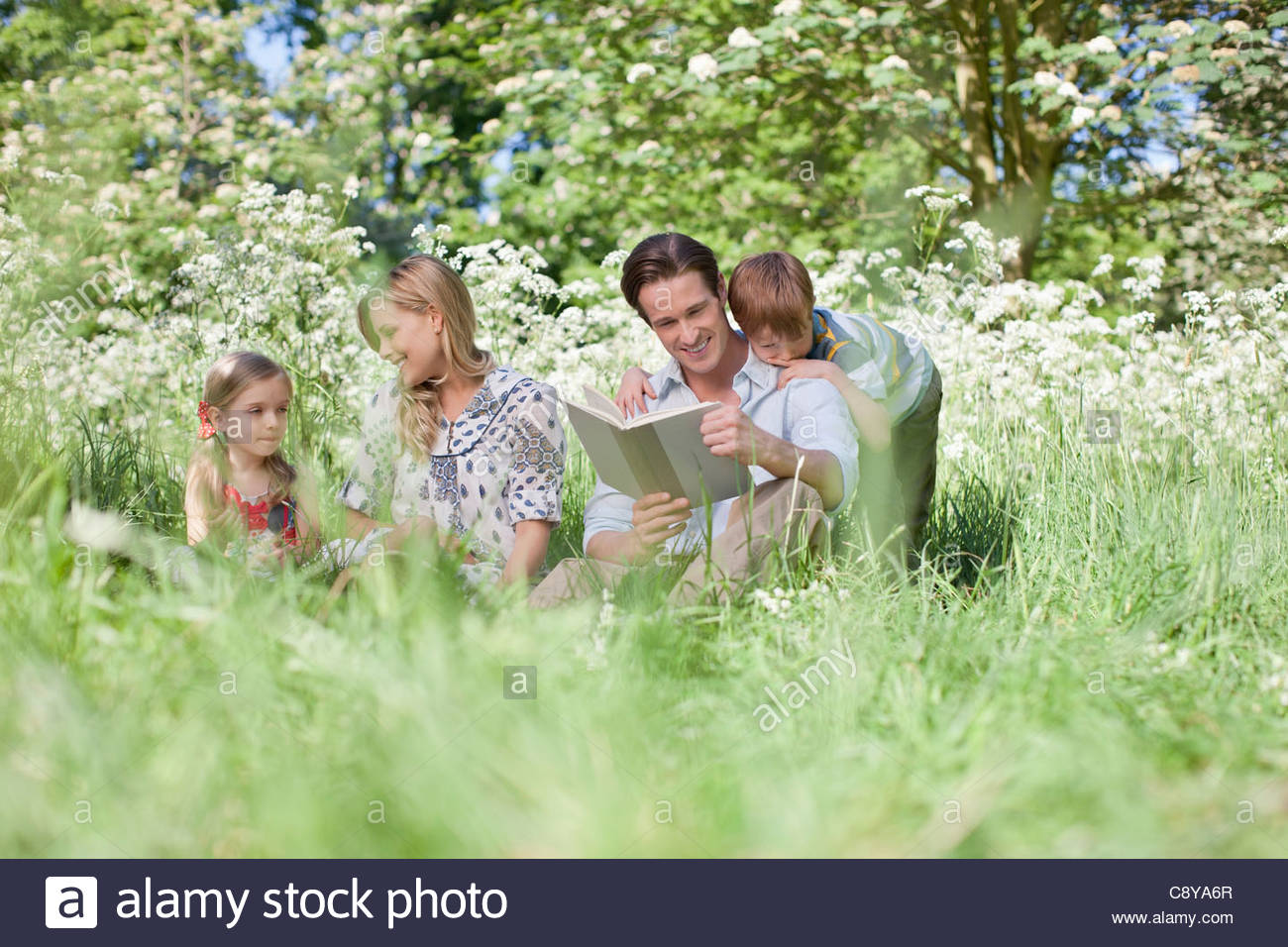 Family relaxing together in grass - Stock Image