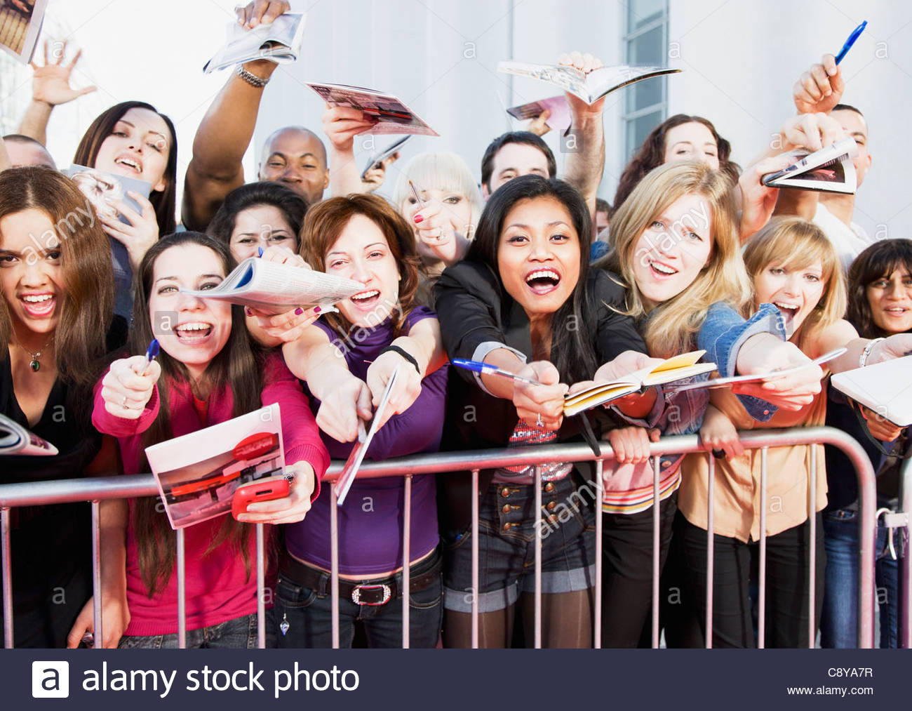 Fans offering notepads for celebrity's signature behind barrier - Stock Image