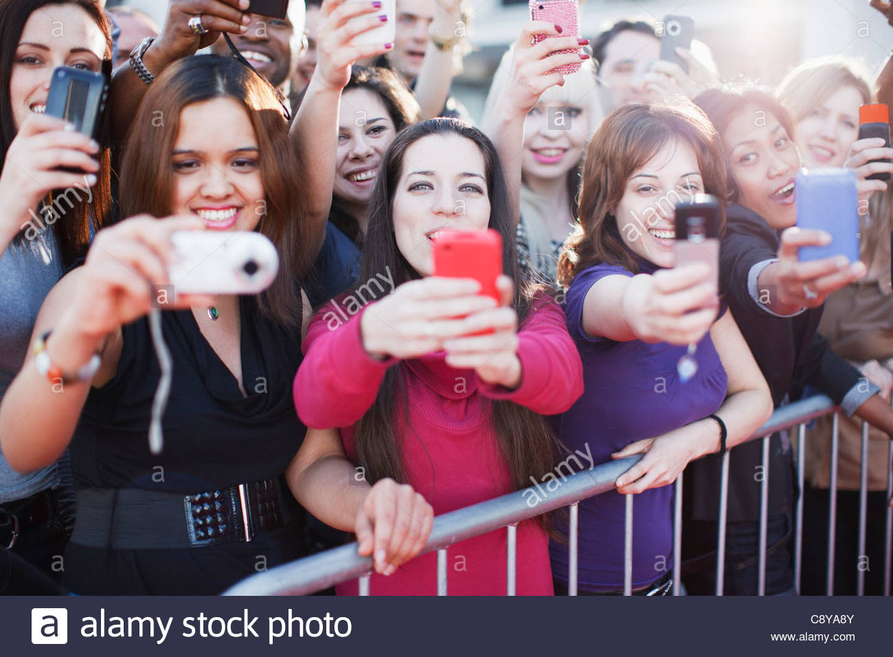 Fans taking pictures with cell phone behind barrier - Stock Image