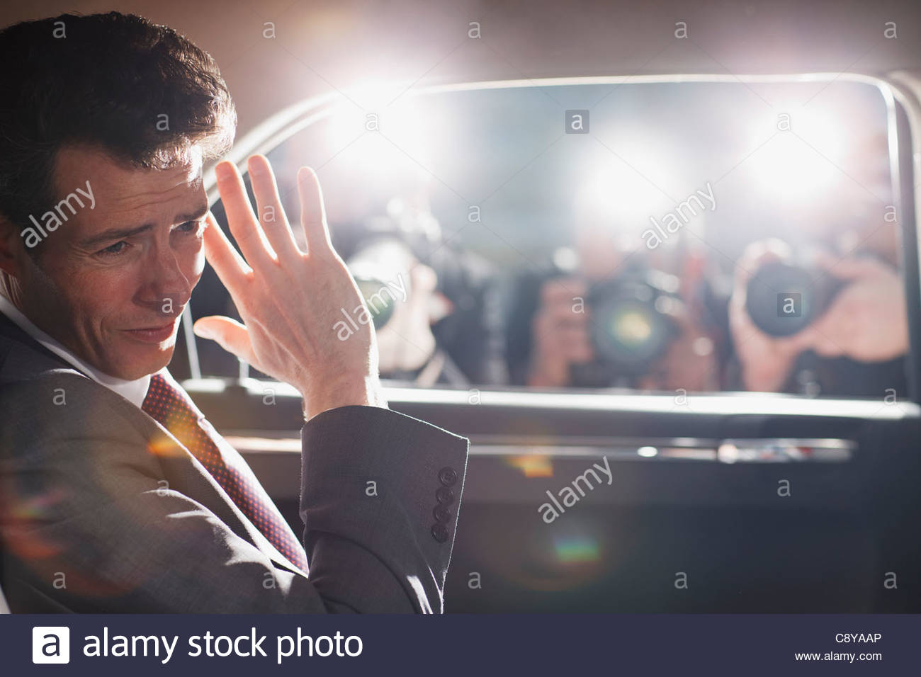 Politician shielding himself from paparazzi - Stock Image