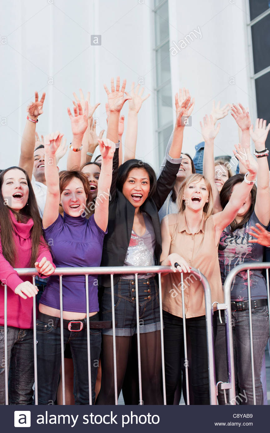 Fans waving from behind barrier - Stock Image