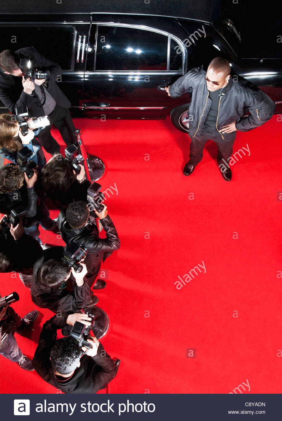 Bodyguard protecting limo from paparazzi - Stock Image