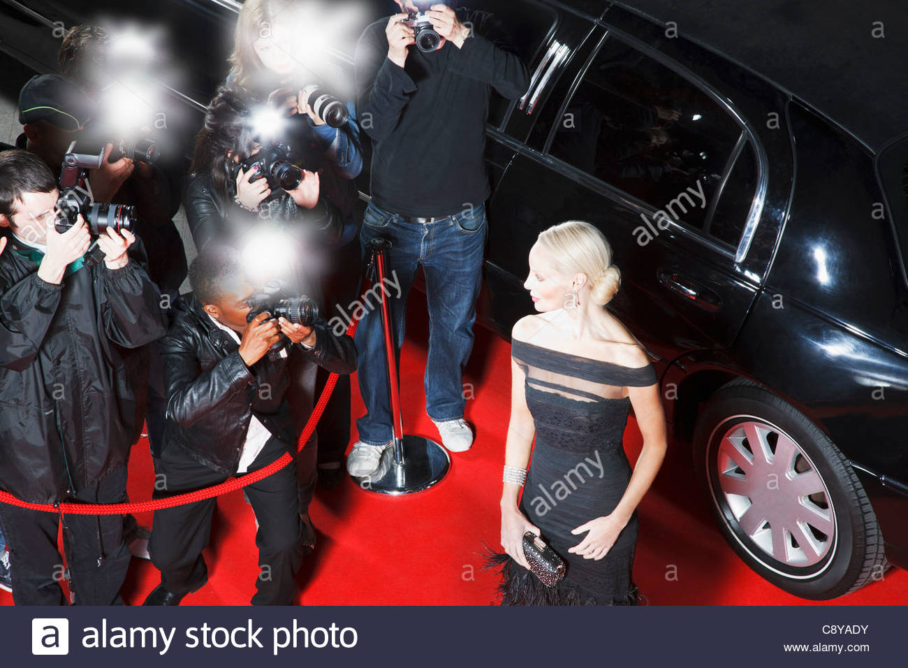 Celebrity posing for paparazzi on red carpet - Stock Image