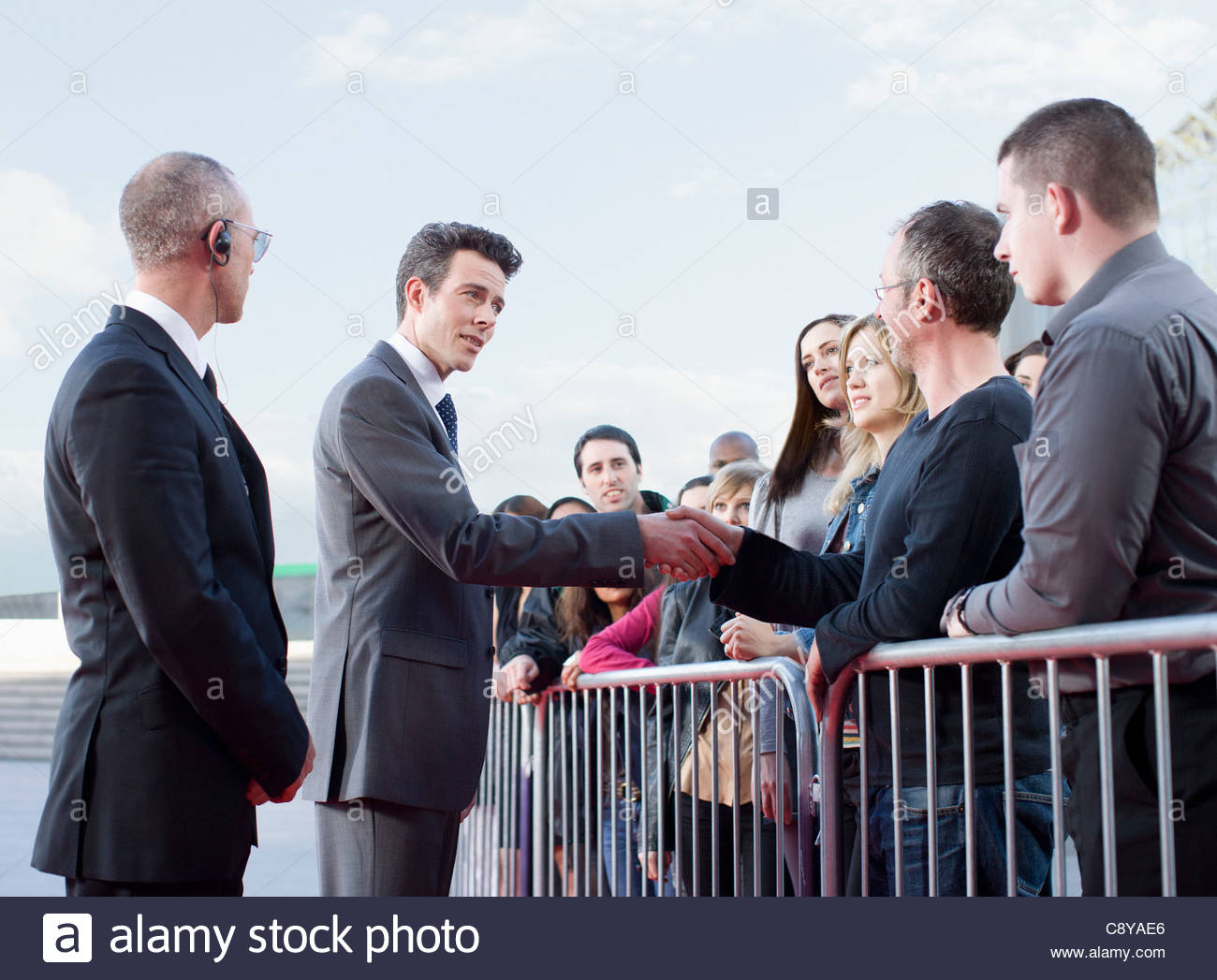 Politician shaking hands with people behind barrier - Stock Image