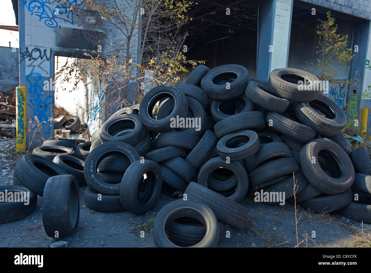 Detroit, Michigan - Old tires dumped outside an abandoned building in an industrial area. - Stock Image