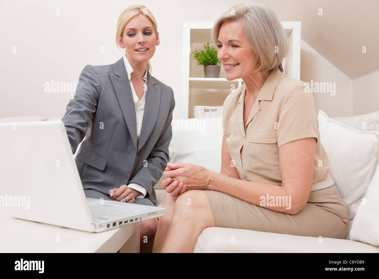 A young saleswoman showing a senior woman medical insurance or pension information on a laptop computer - Stock Image