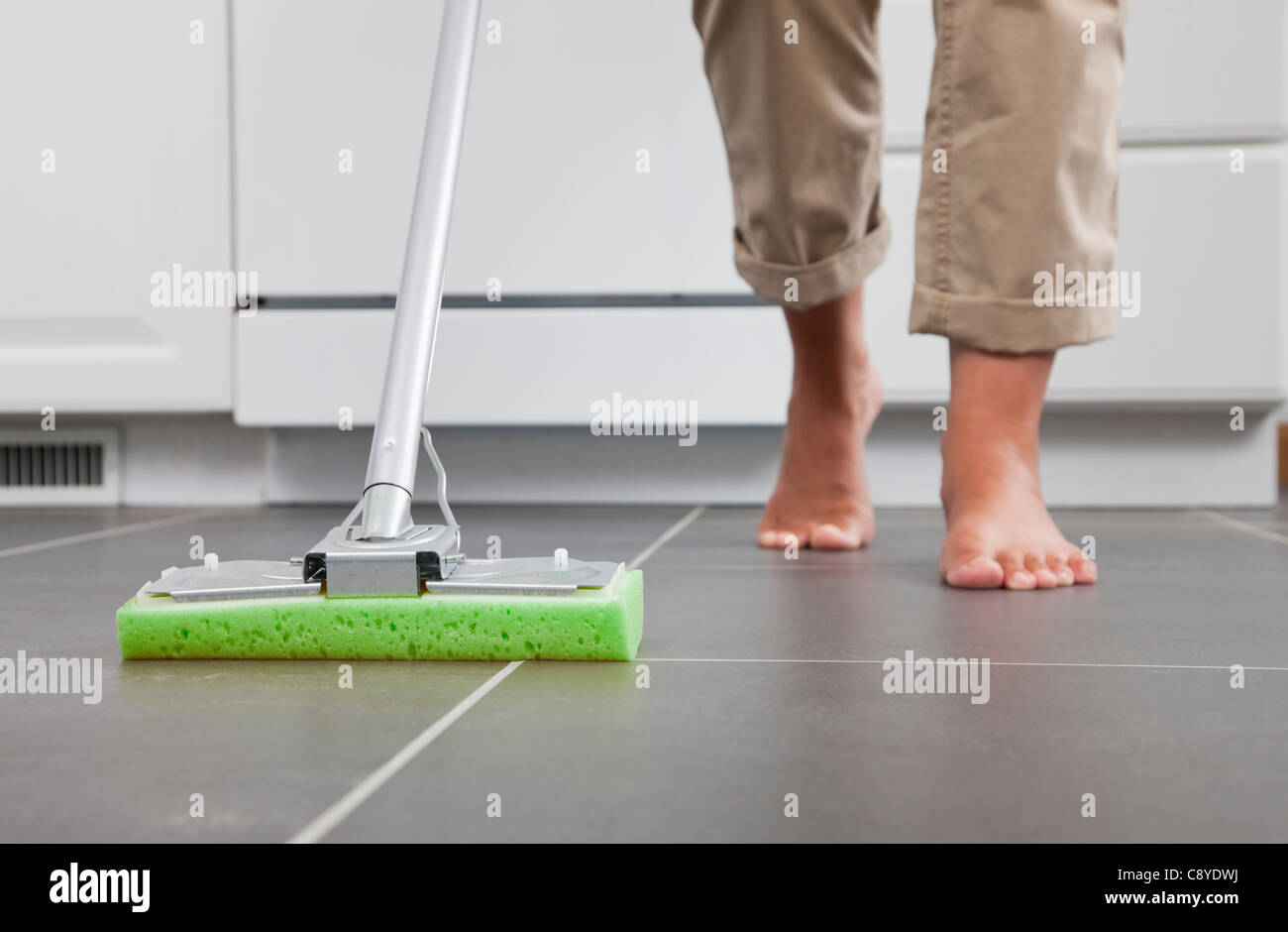 USA, Illinois, Metamora, Barefoot woman cleaning kitchen floor, low section - Stock Image
