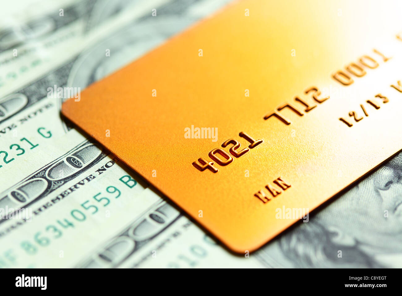 Gold credit card on dollar notes. Shalow DOF! - Stock Image