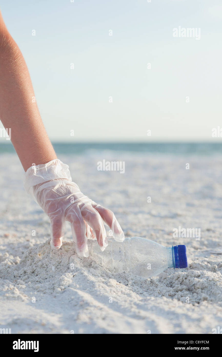 USA, Florida, St. Petersburg, Girl (10-11) cleaning beach, close-up of gloved hand reaching for plastic bottle - Stock Image