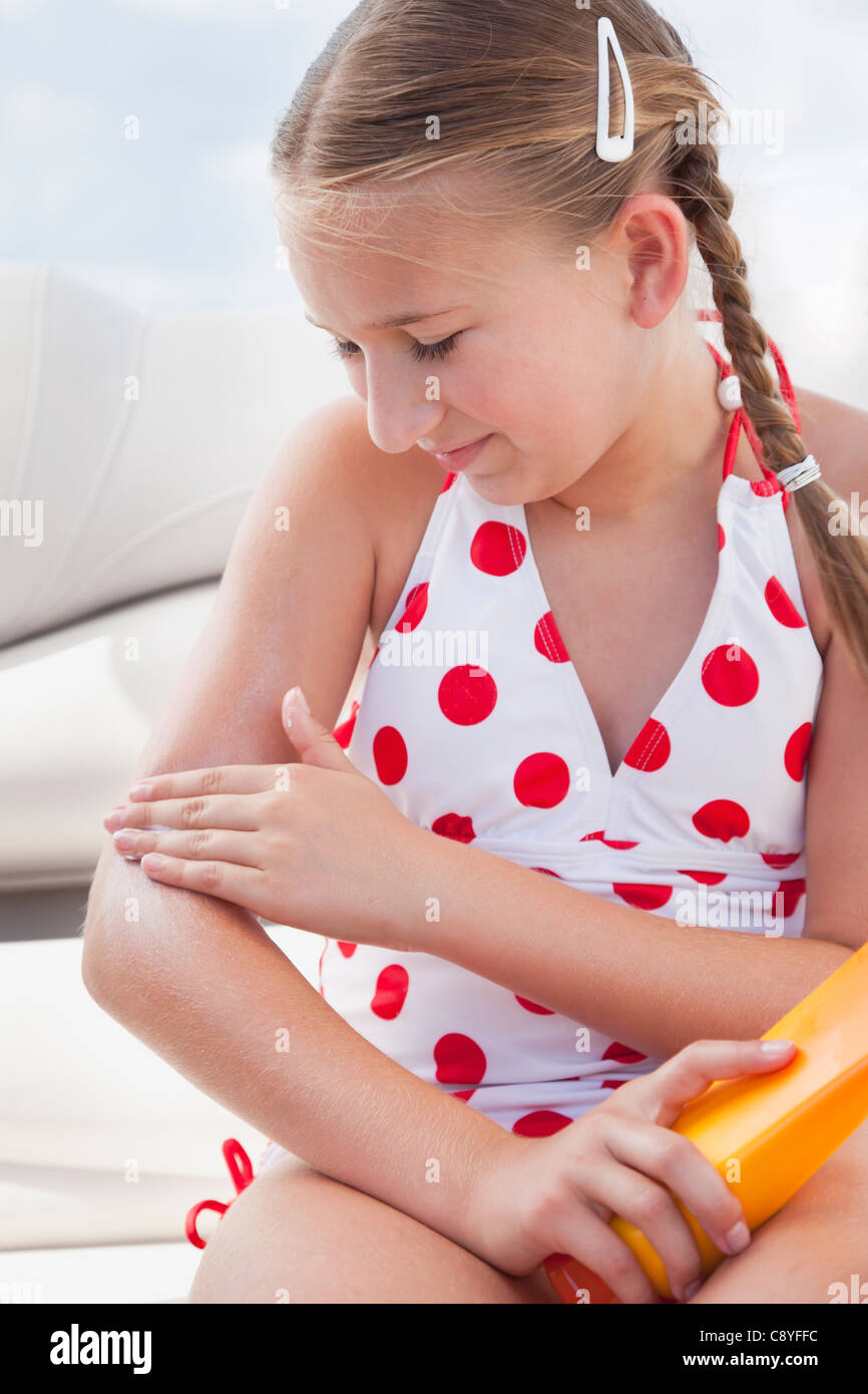 USA, Florida, St. Petersburg, Girl (10-11) applying sun lotion on arm - Stock Image