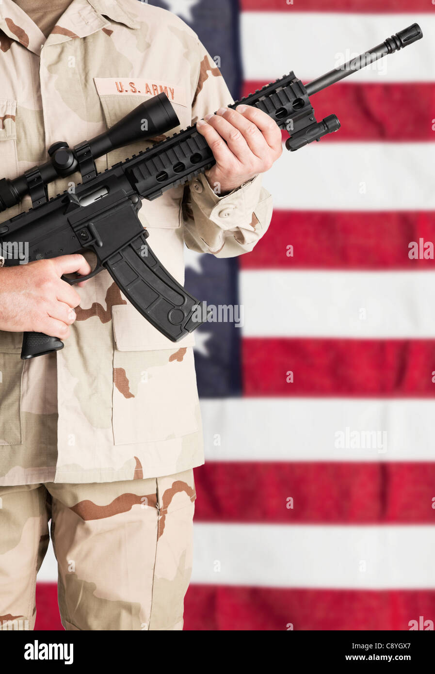 Studio shot of soldier with machine gun standing against American, mid section - Stock Image
