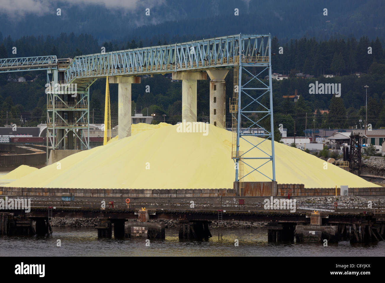 A sulfur pile is processed on the waterfront in Vancouver, Canada - Stock Image