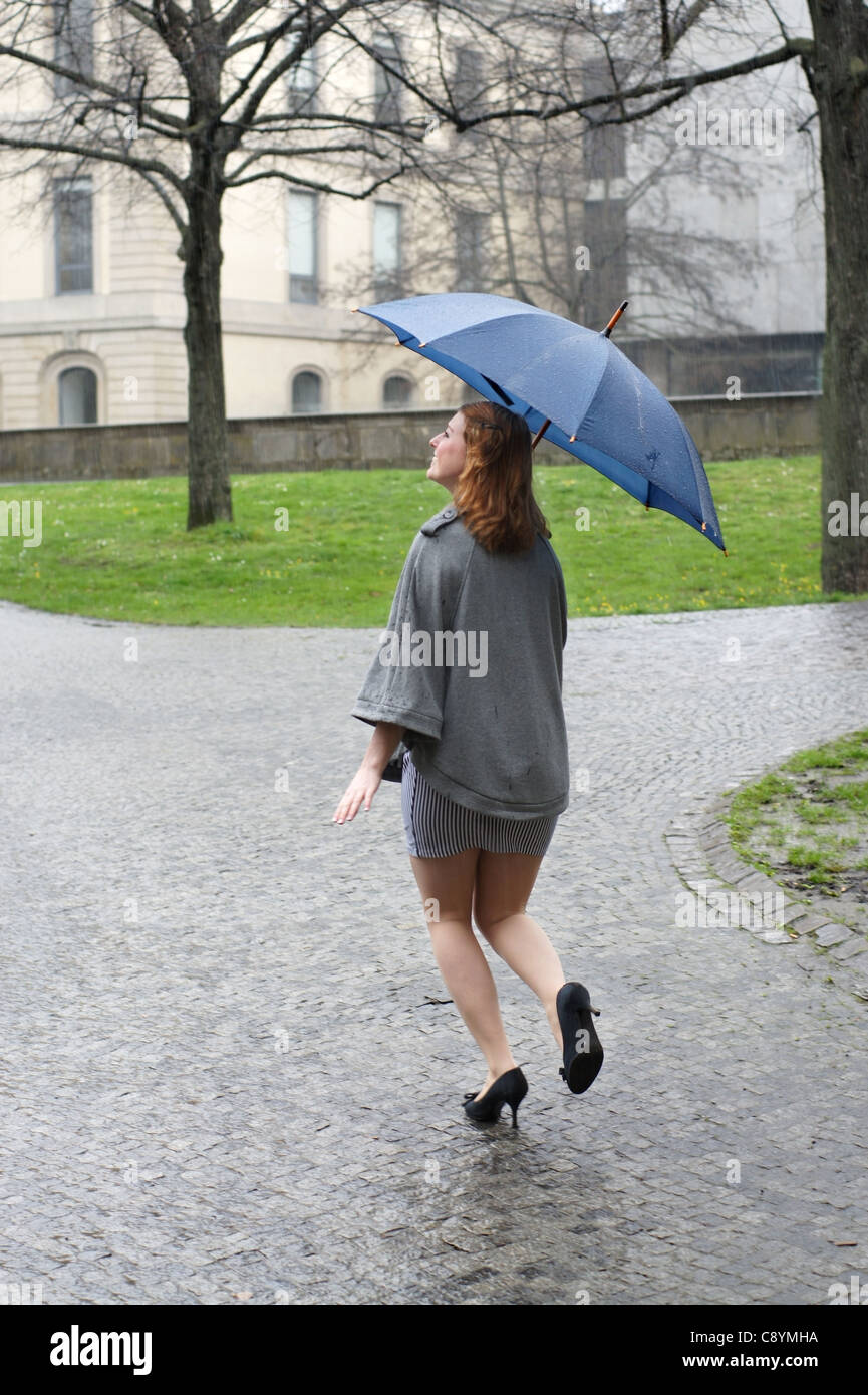 young woman with umbrella running through the rain Stock Photo