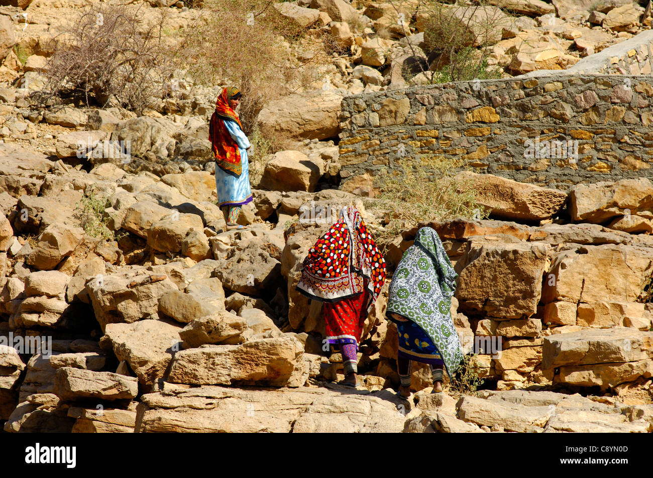 Omani women in colorful garments on a rocky trail the way to their mountain village in the Hajjar Mountains, Sultanate - Stock Image