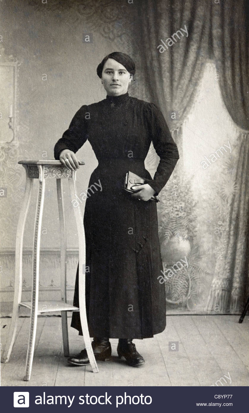 classical vintage studio portrait of a full length standing female person - Stock Image