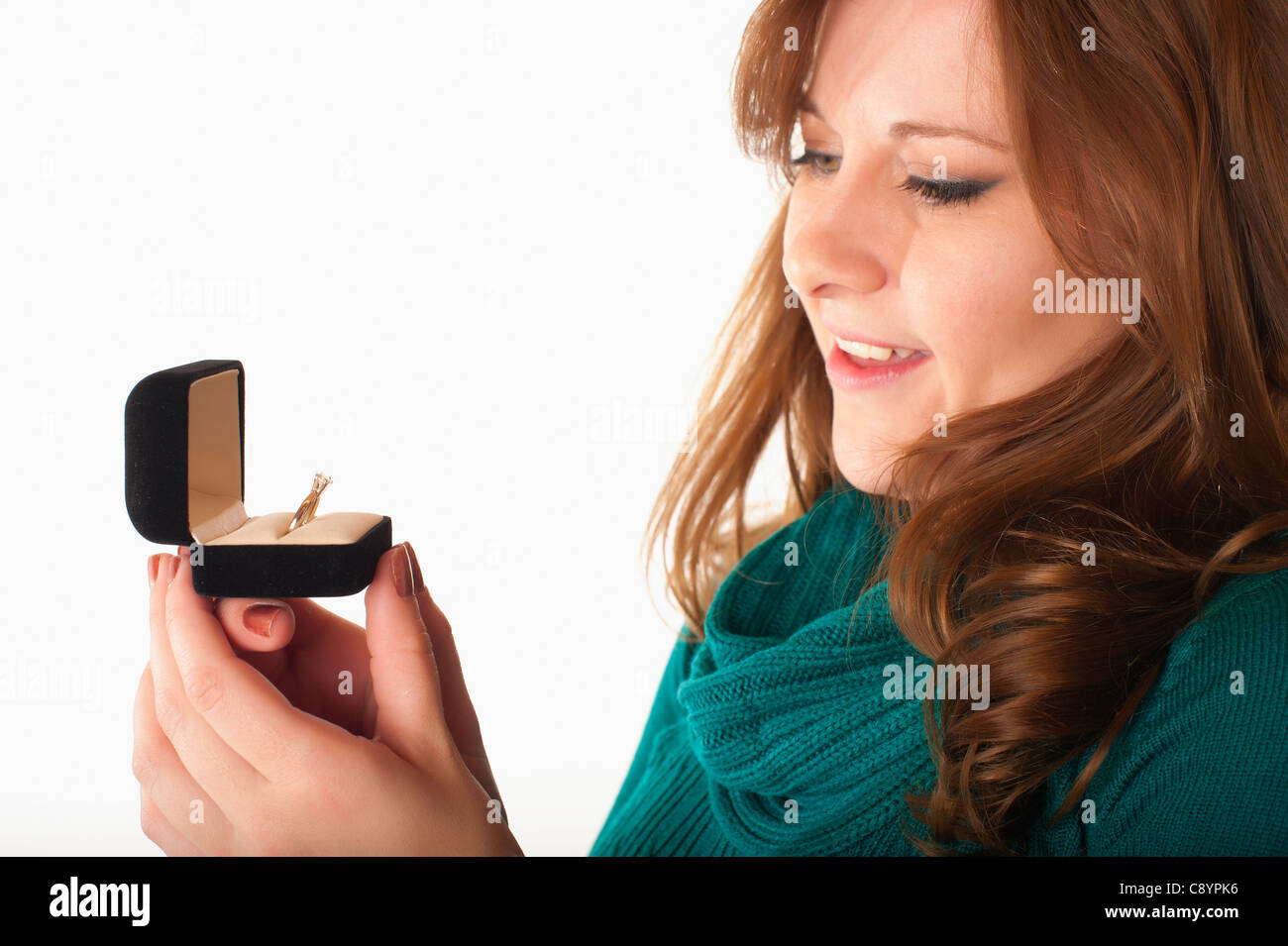 Young woman looking at diamond ring in jewelry gift box - Stock Image
