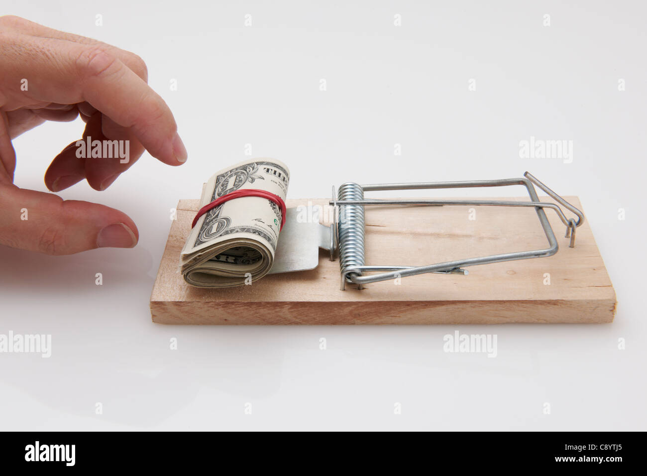 Male hand taking rolled up dollar bills from mousetrap Stock Photo