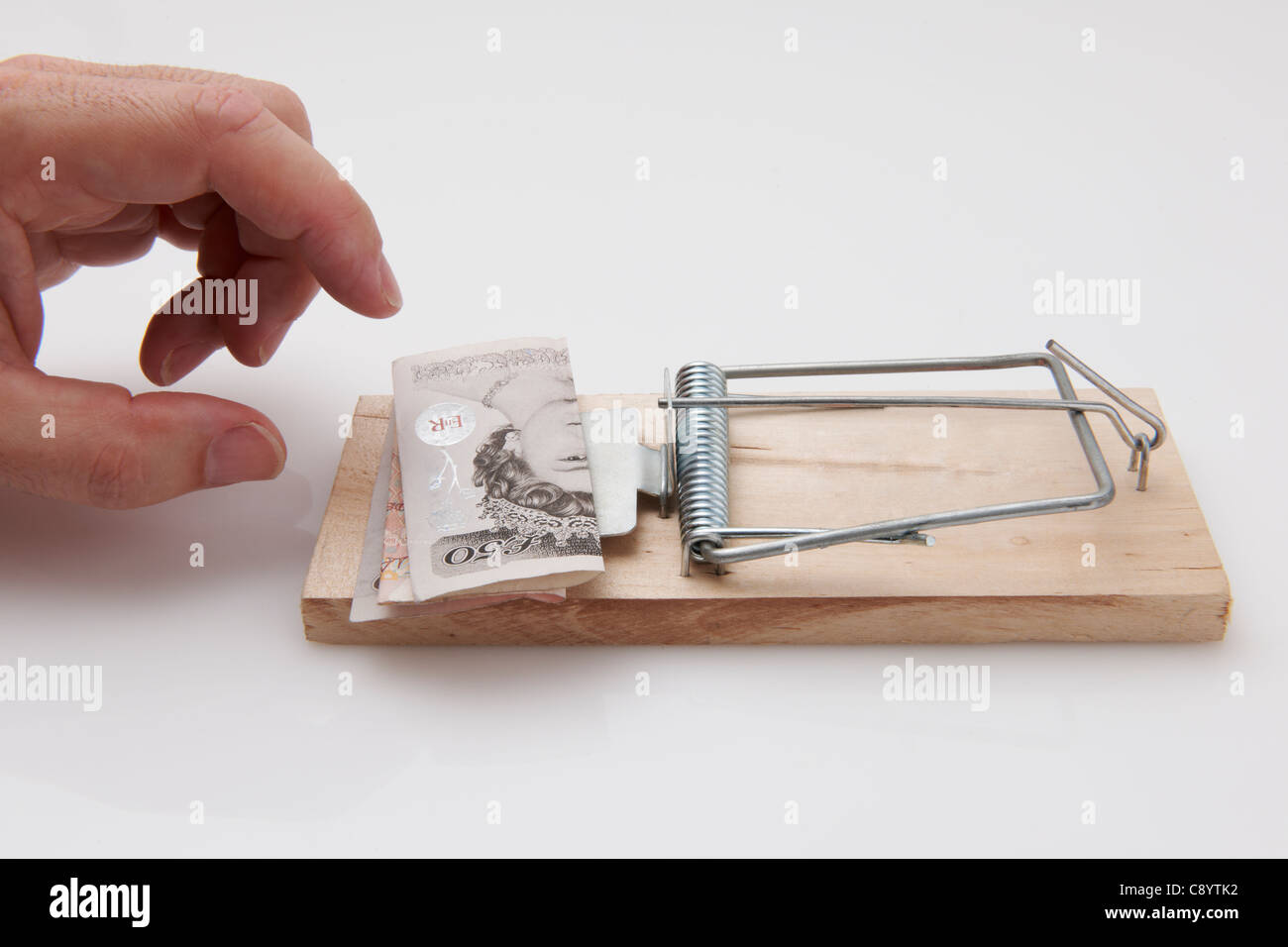 Male hand taking fifty pound note from mousetrap Stock Photo
