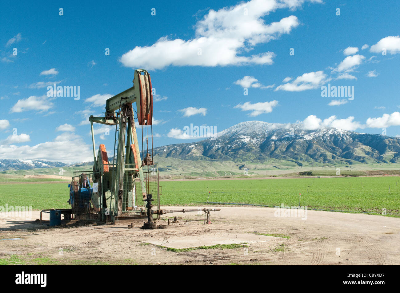 oil derrick outside Bakersfield with snow covered mountain and green fields in background.  Good depiction of CLEAN - Stock Image