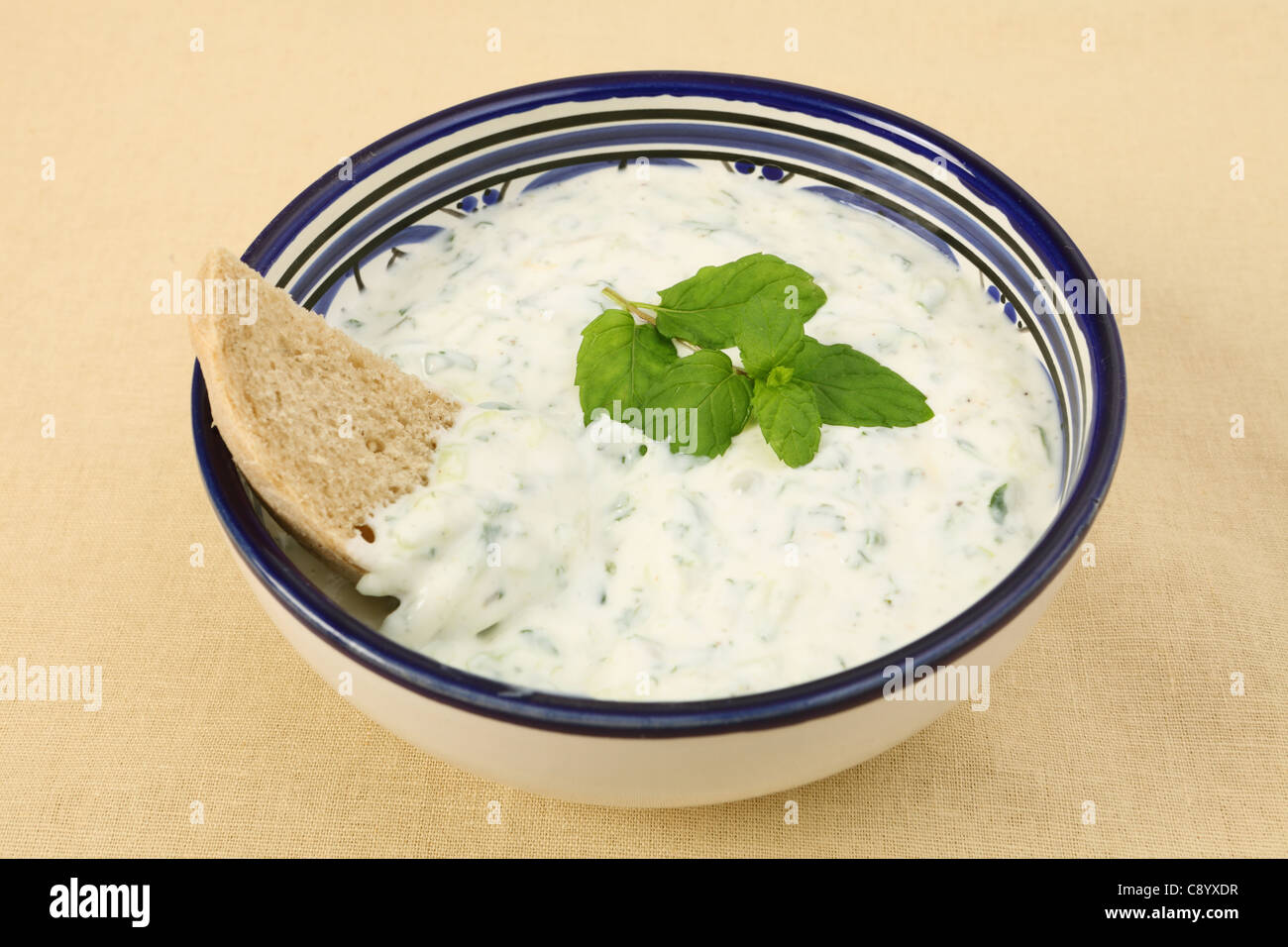A bowl of tzatziki yoghurt and cucumber dip with a slice of brown farmhouse bread on a woven tablecloth - Stock Image