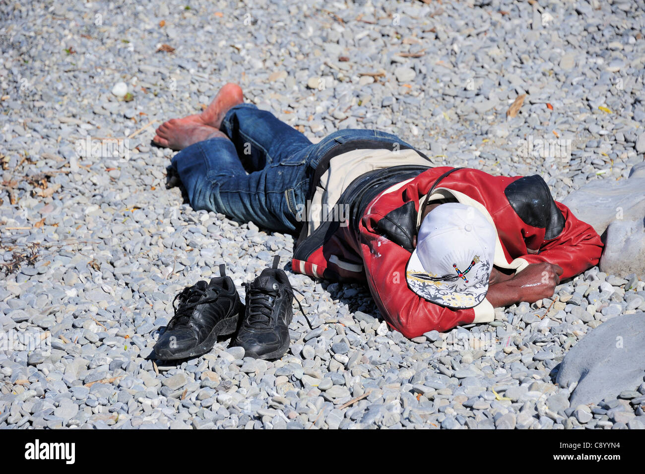 An asylum seeker lying on a pebbly beach with his shoes beside him - Stock Image