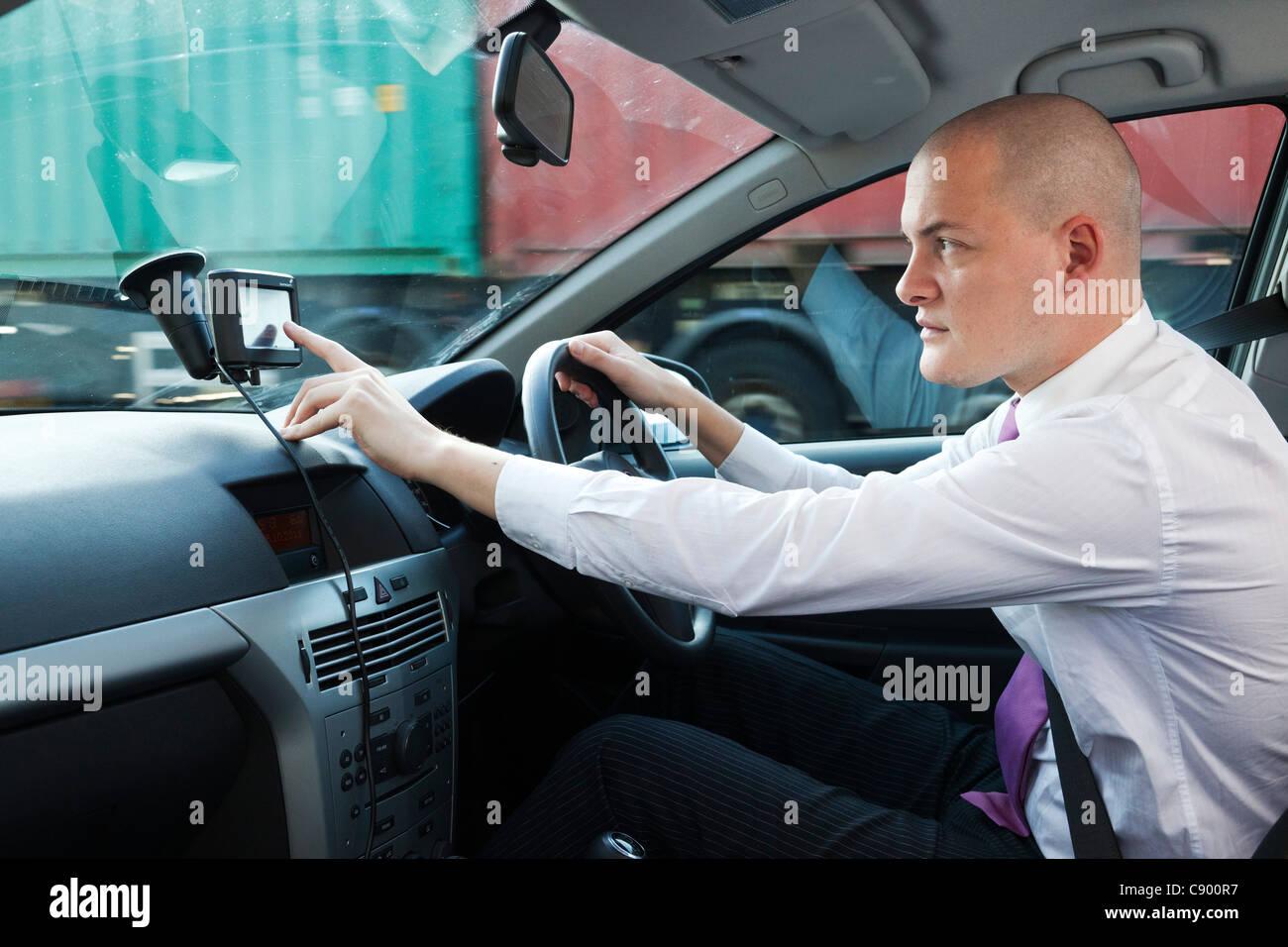 man using GPS satnav  whilst driving car on motorway - Stock Image