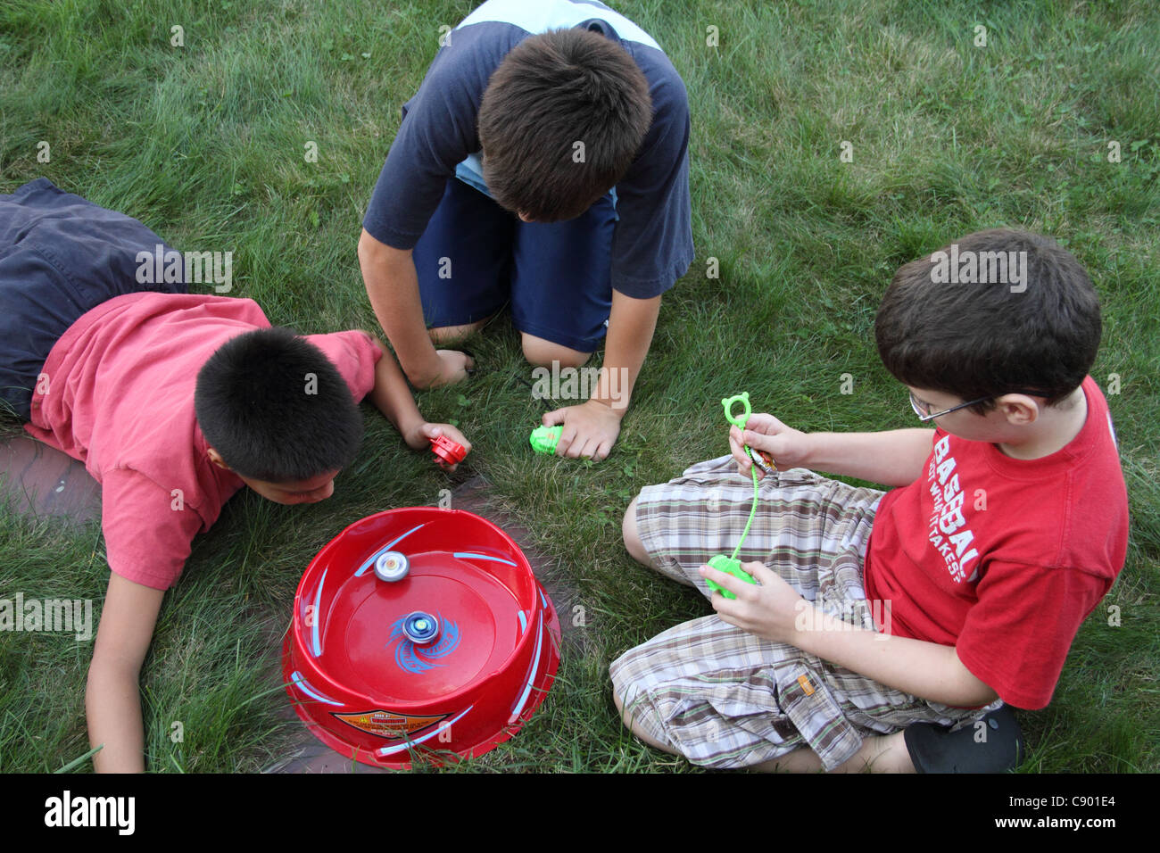 Bey Blade fun three boys 9-10 playing game friendship - Stock Image