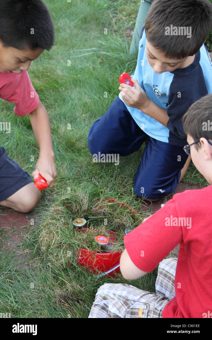 let it rip with Bey Blade friends adding grass to stadium vertical - Stock Image