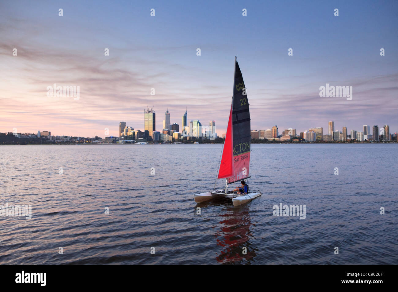 Catamaran sailing boat on the Swan River at sunset with the city in the distance. - Stock Image