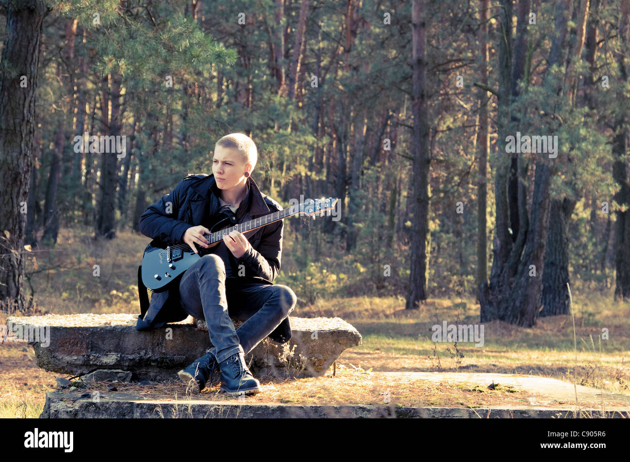teen musician plays the guitar in the autumn forest - Stock Image