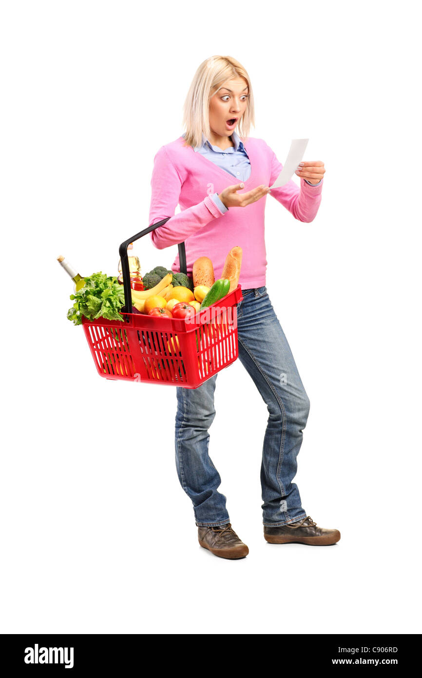 Full length portrait of a surprised woman looking at store receipt and holding a shopping basket - Stock Image