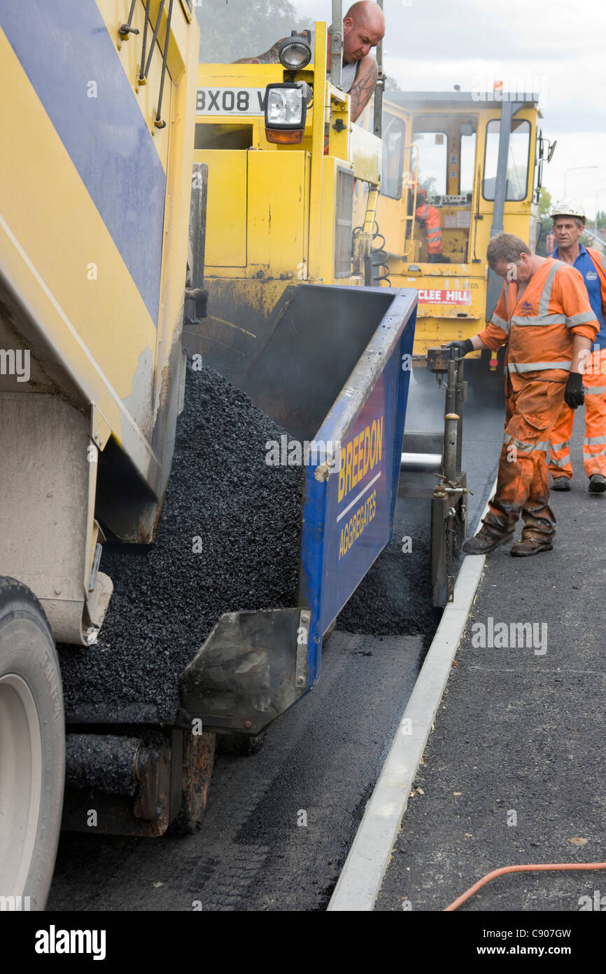 Guide of tarmac laying machine running along side of kerb. - Stock Image
