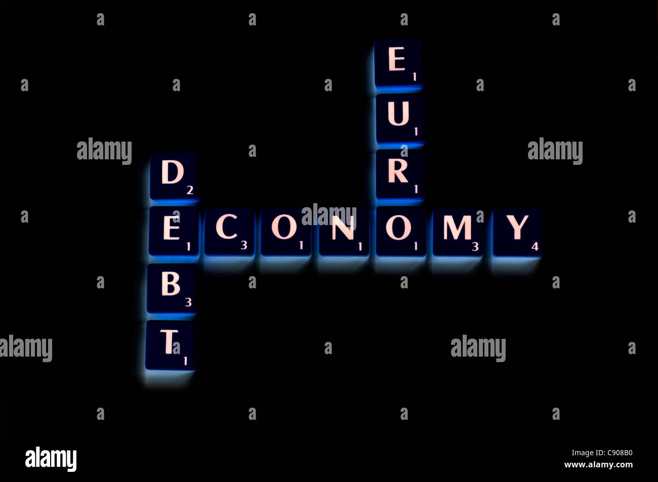 Inverted Scrabble tiles spelling out the words euro, economy and debt - Stock Image