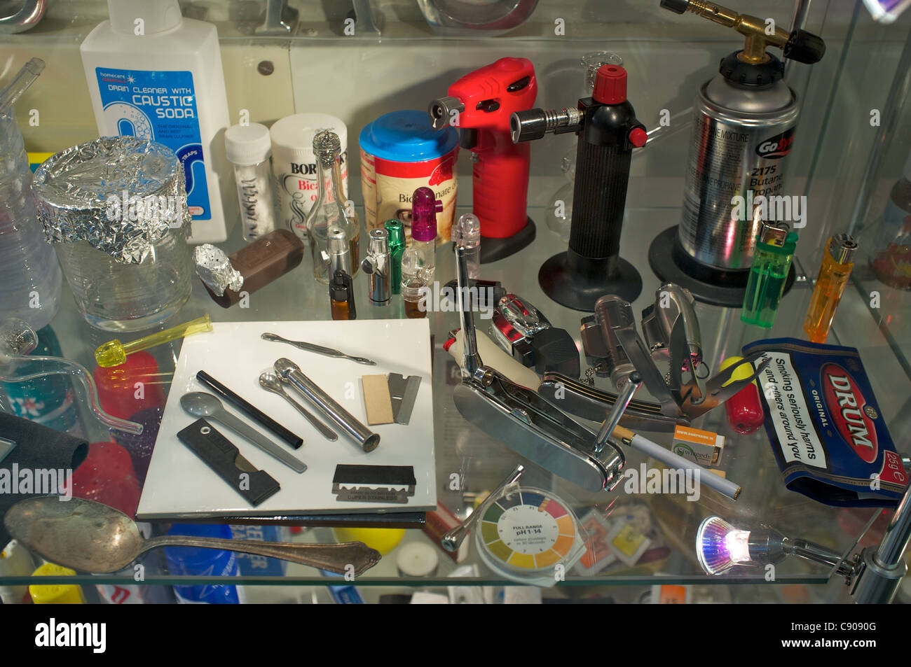 Illicit drugs paraphernalia in glass cabinet at research lab in London. - Stock Image