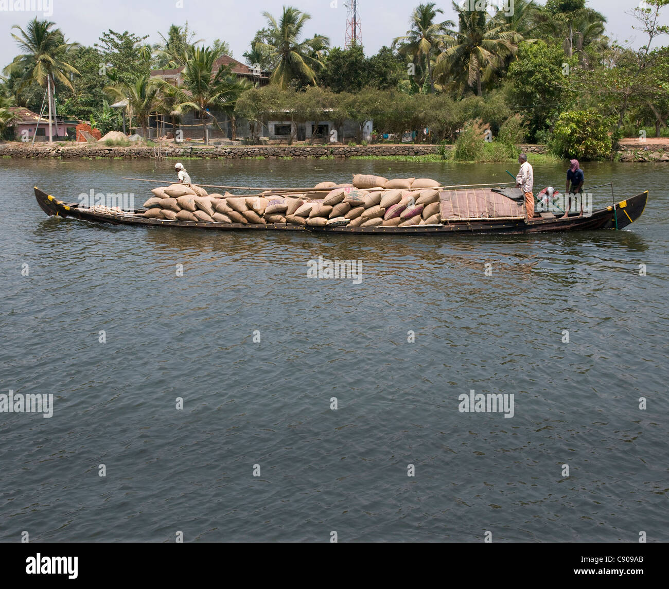 Rice sacks being transported in an 'original' rice boat along the backwaters in the RIce Belt area of Kerala - Stock Image