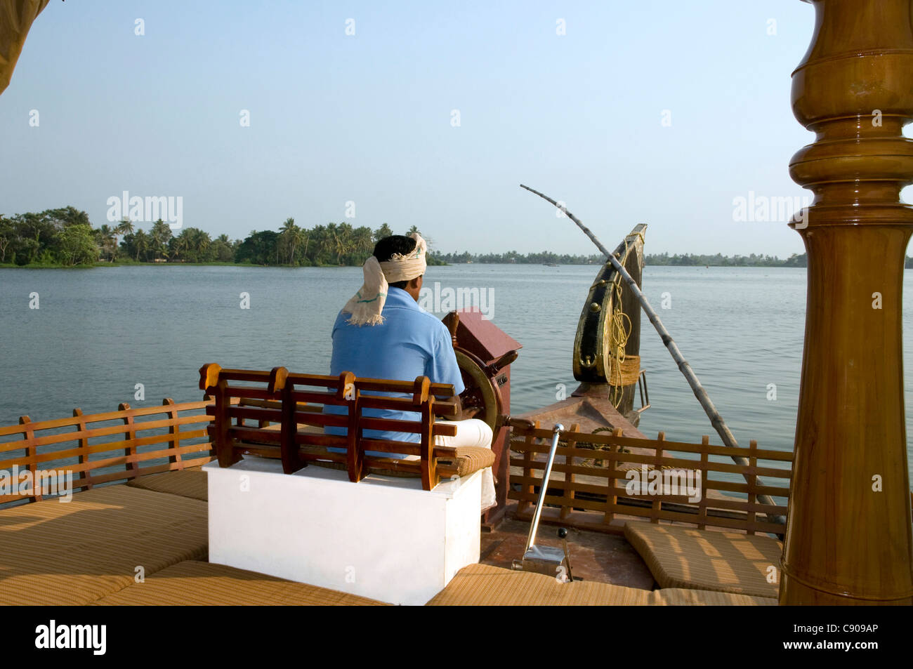 Skipper steering the Kettuvallam,house boat in the Kerala Backwaters at  Lake  Vembanad, India - Stock Image