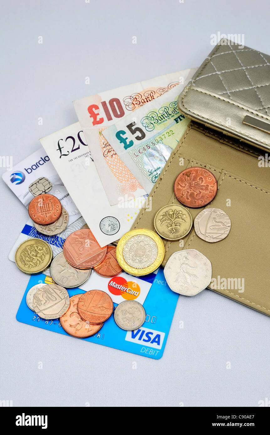 money and credit cards spilling out of a purse - Stock Image