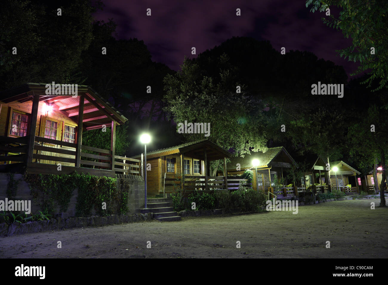Log cabins on a camping site at night - Stock Image