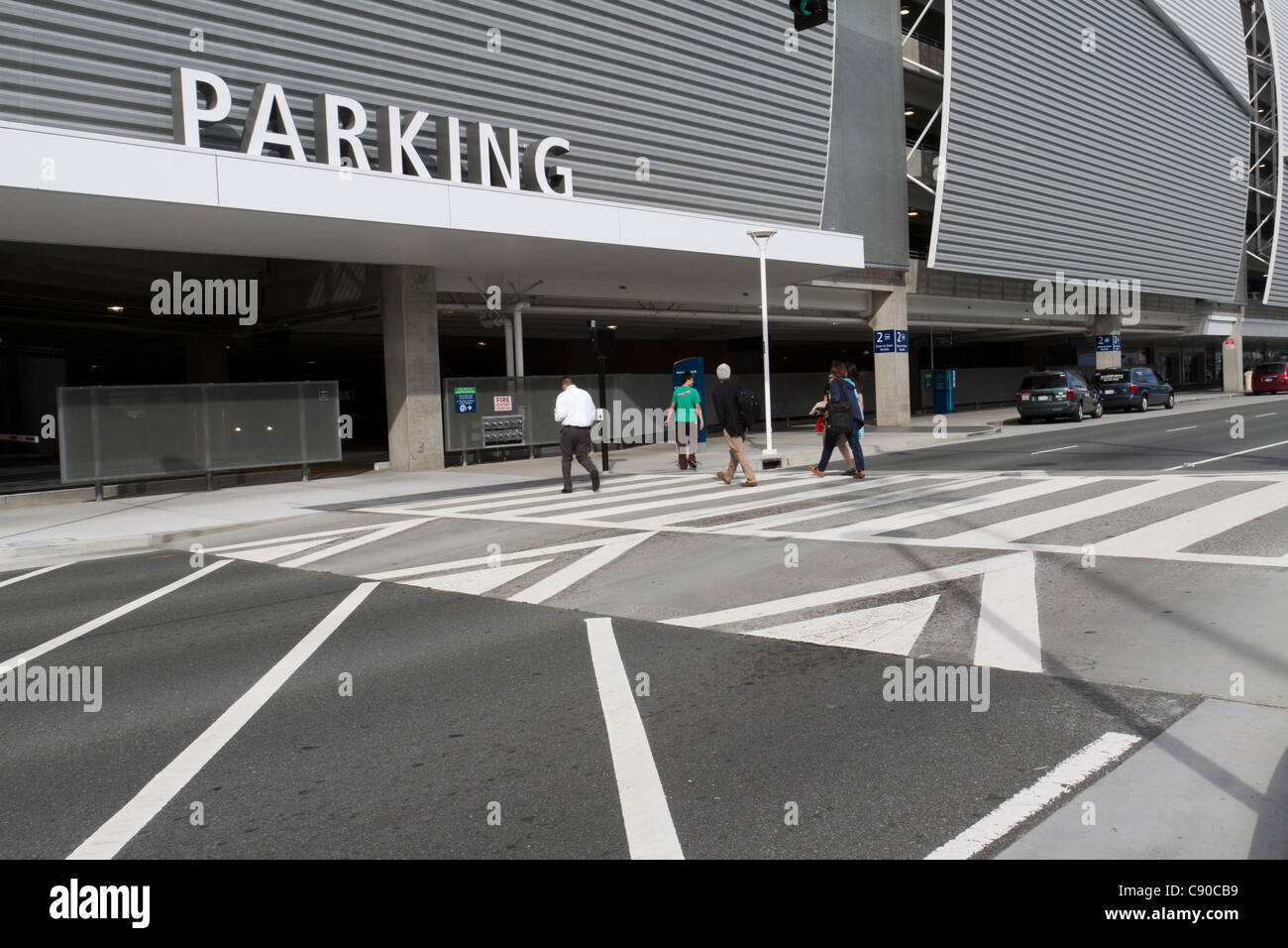 People walking across crosswalk toward parking structure at San Jose Airport in California - Stock Image