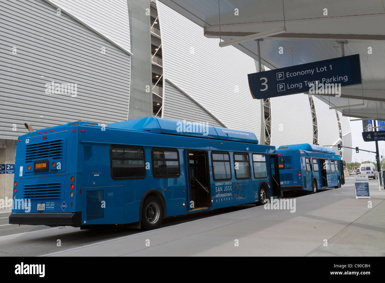 Blue shuttle buses waiting at the curb to go to the long term parking area at San Jose International Airport in - Stock Image