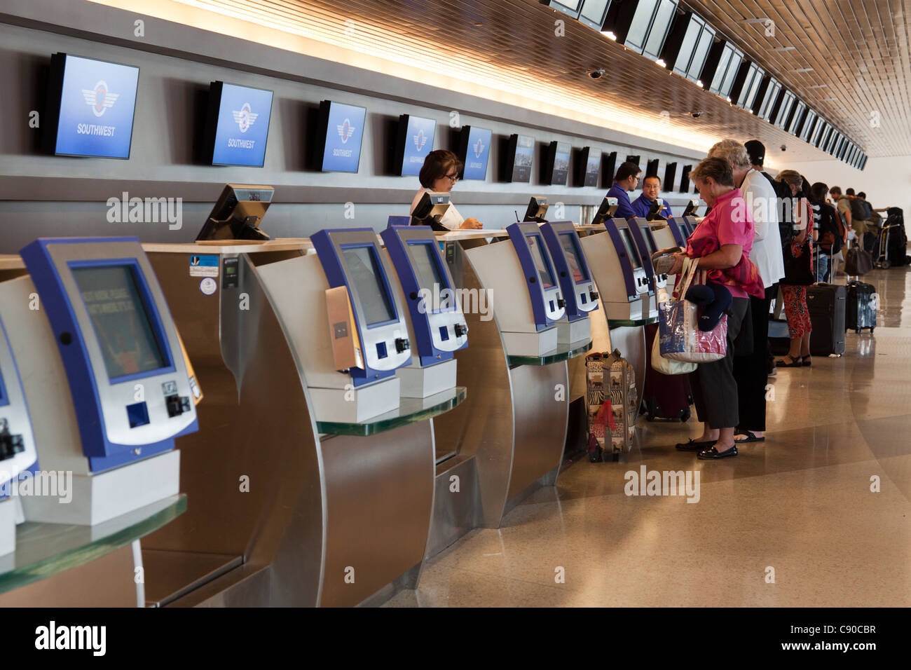 People checking in to their flights using kiosks at the self-serve ticket counter in San Jose Airport in California - Stock Image