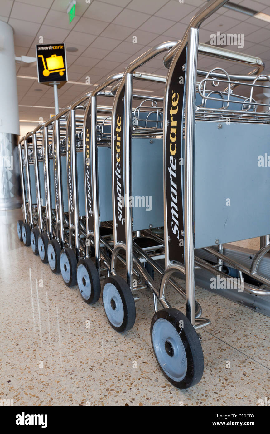 Stacked row of SmarteCartes available for carrying luggage at an airport terminal - Stock Image
