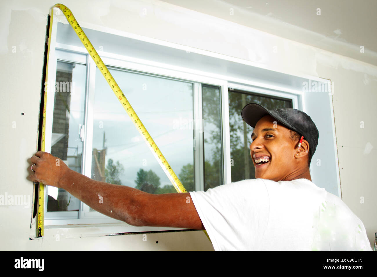 Worker holding a tape measure against wall to take measurement - Stock Image