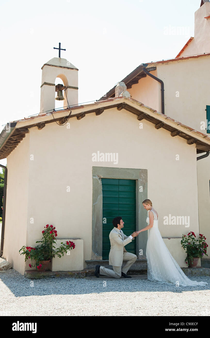 Newlyweds outside church, groom on one knee - Stock Image