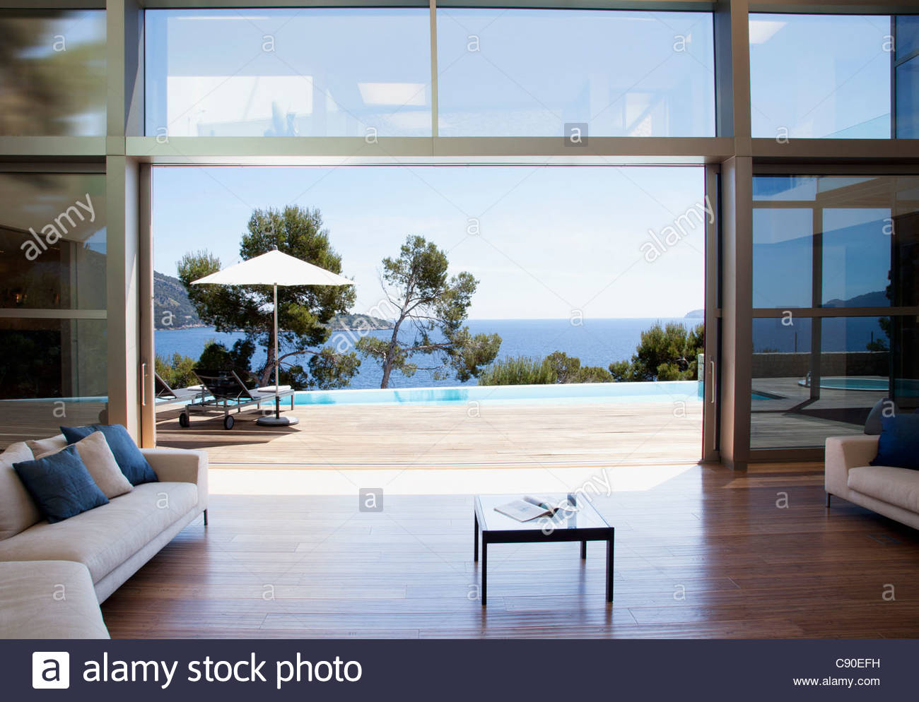 sofa and sliding doors in open modern house - Stock Image